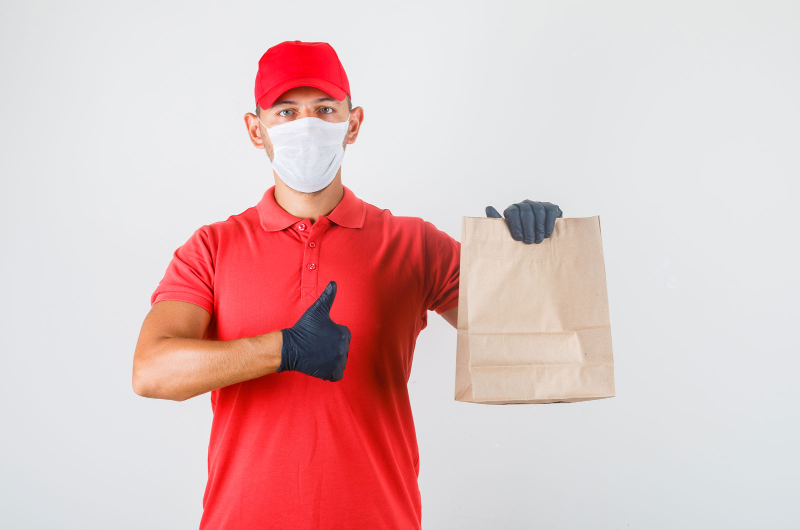 Delivery man holding paper bag and showing thumb up in red unifo